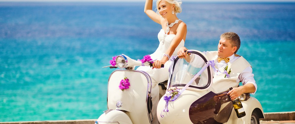 Bride and groom riding vespa on the beach